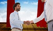 stock photo of curtains stage  - Young businessmen shaking hands in office against stage with red curtains - JPG