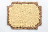 picture of millet  - Figured frame made of burlap and millet grains lie on a white background - JPG