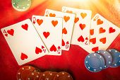 picture of flush  - Beams of heavenly light illuminate a winning hand straight flush of hearts - JPG