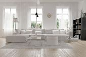 foto of architecture  - Modern spacious lounge or living room interior with monochromatic white furniture and decor below three tall bright windows with a dark bookcase accent in the corner - JPG