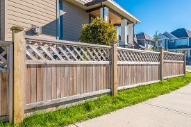 foto of wooden fence  - wooden fence with green lawn and houses - JPG