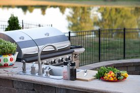 picture of braai  - Preparing a healthy summer meal in an outdoor kitchen with gas barbecue and sink on a brick patio overlooking a tranquil lake with tree reflections - JPG