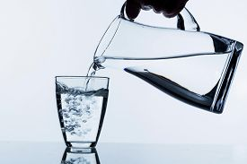 picture of tapping  - pure water is emptied into a glass of water from a jug - JPG