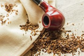 image of tobacco-pipe  - Tobacco pipe on rustic warn wood surface with spilled natural tobacco - JPG