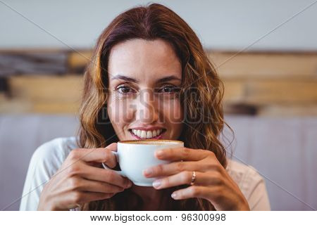 Pretty brunette having coffee at the cafe