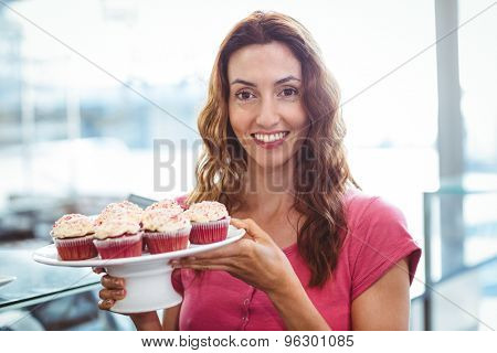Pretty brunette showing plate of pastries at the bakery