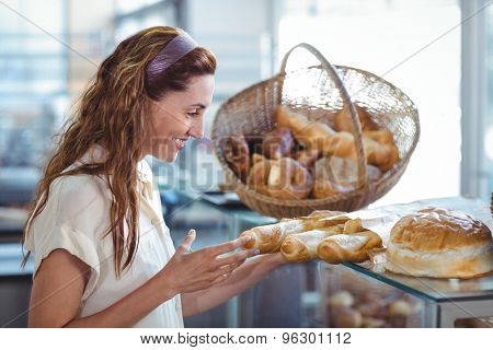 Pretty brunette pointing at loaf of bread in the bakery