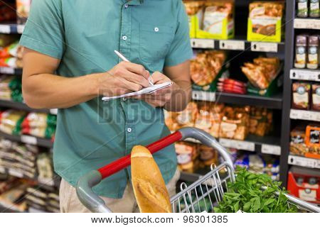 Man writing in his notepad in aisle at supermarket