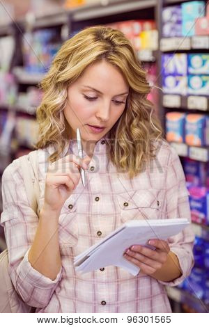 Smiling pretty blonde woman writing on her notepad and thinking in supermarket