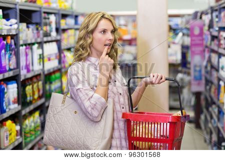 Side view of a pretty blonde woman having a shopping bag and looking ar shelf in supermarket