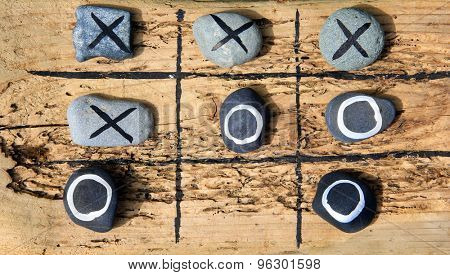 Tic tac toe game made from drift wood and rocks for outdoor garden play.