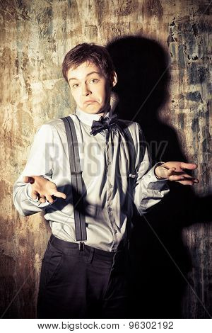 Elegant young man stands by the grunge wall and wonders.