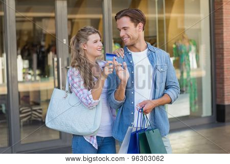 Happy couple showing their new credit card at the mall
