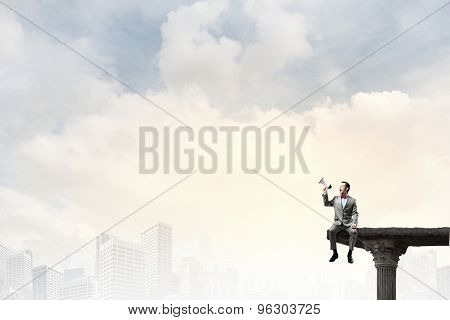 Businessman sitting on rock edge and screaming in megaphone