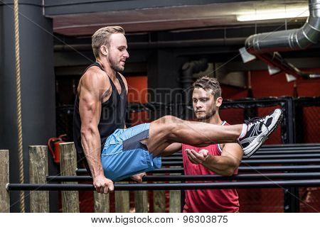 Trainer supervising a man doing exercises on parallel bar