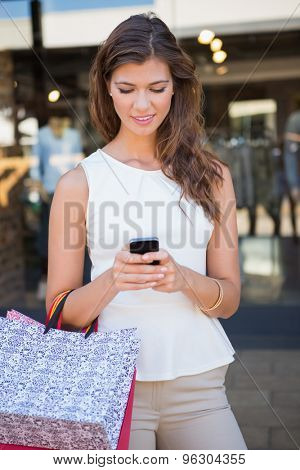 Smiling woman with shopping bags using smartphone at the shopping mall