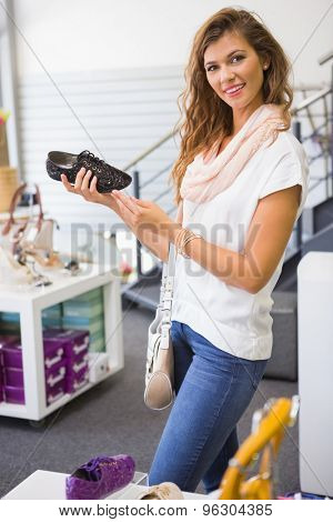 Portrait of smiling woman holding laced shoe and looking at camera at a shoe shop