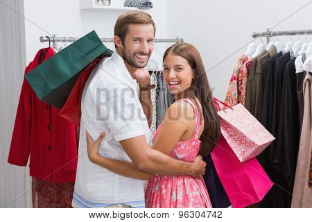 Portrait of smiling couple with shopping bags embracing at a boutique