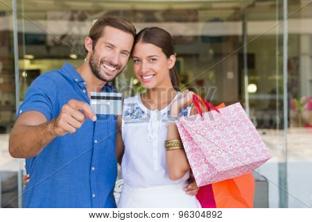 Young happy couple looking camera after shopping holding a credit card