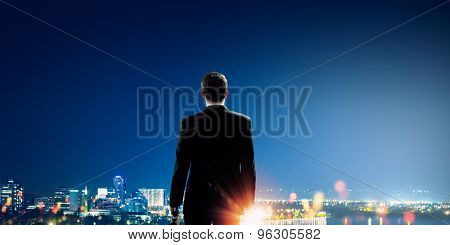 Rear view of businessman looking at night city