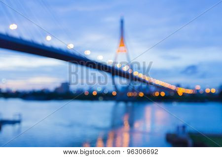 Abstract blur bokeh background, Suspension Bridge with water reflection during twilight