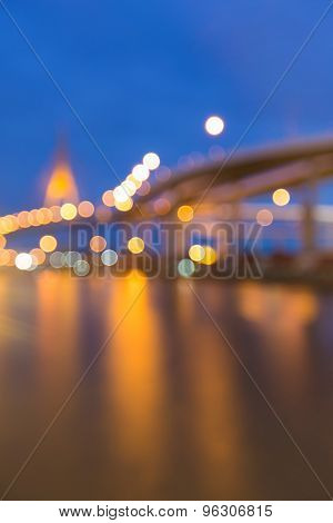 Abstract blurred bokeh lights of suspension bridge and highway curved at twilight