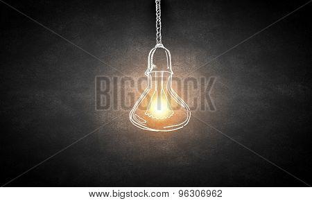 Illuminating hanging light bulb on dark background