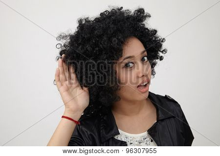Happy girl with big afro hair trying to listen something
