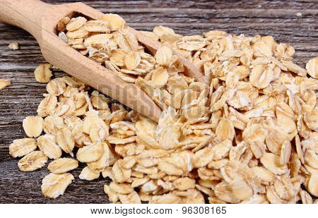 Oat Flakes With Spoon On Wooden Background