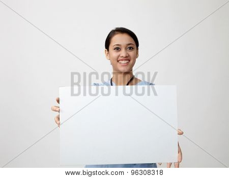 Nurse showing medical sign billboard standing, Young smiling woman nurse or doctor in scrubs showing empty blank sign board with copy space. Indian model isolated on white background