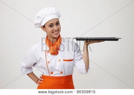 Portrait of a Indian woman with chef uniform holding an empty tray