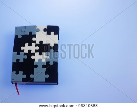 jigsaw puzzle note book on the blue background