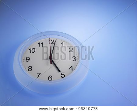 Clock showing 5 o'clock on a blue wall