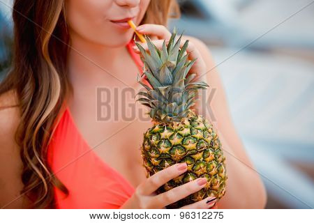 Portrait of young beautiful woman drinking fresh pineapple cocktail