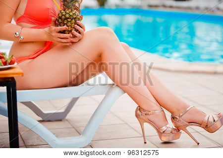 Perfect, sexy legs and body of young woman wearing seductive red swimsuit, drinking fresh pineapple