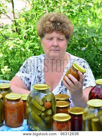 Mature housewife with canned food for the winter