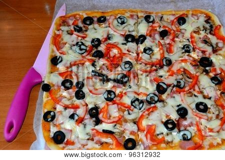 Pizza with ham, mushrooms, olives, cheese and peppers