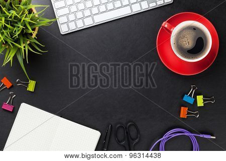 Office leather desk table with computer, supplies, coffee cup and flower. Top view with copy space