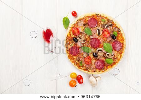 Italian pizza with pepperoni, tomatoes, olives, basil and red wine on wooden table. Top view with copy space