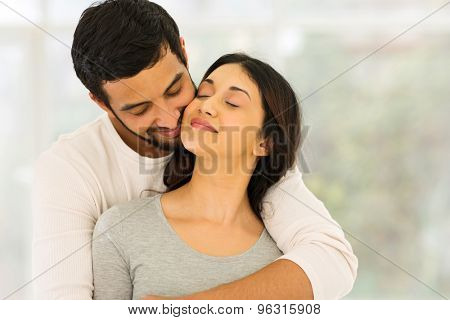 loving young indian couple embracing at home