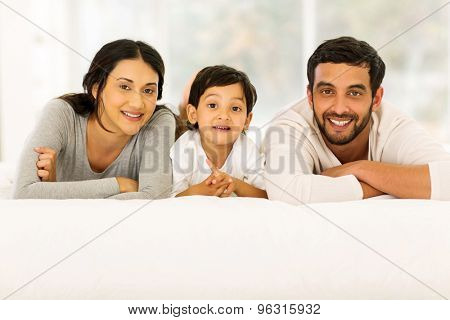portrait of beautiful young indian family relaxing on bed