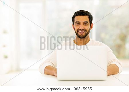 happy young indian man relaxing at home with laptop