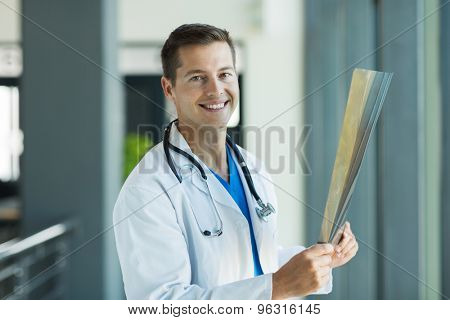 cheerful medical intern holding x-ray in clinic