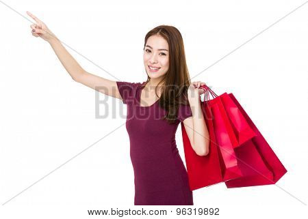 Young woman with finger point up and hold with shopping bag