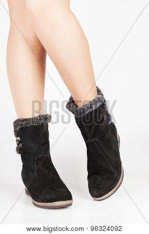 Beautiful female legs in black suede boots on a white background