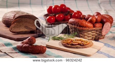 still life sliced sausage on a cutting board with rosemary, bread and tomatoes