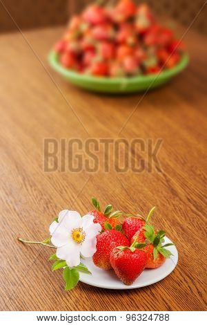 several strawberries on a plate on a table with a flower. in the background lots of strawberry