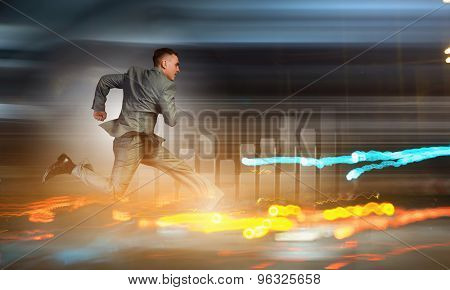 Young businessman in suit running at full pelt
