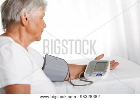 Elder Woman Measuring Blood Pressure With Automatic Manometer At Home