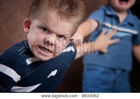 Angry Little Boy Glaring And Fighting With His Brother